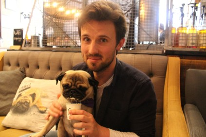 pug owner with pug licking puggucino at pop up pug cafe