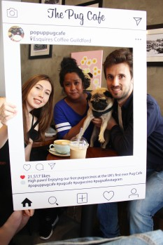 friends hold pug at pop up pug cafe