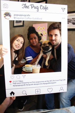 friends hold pug at pop up pug cafe