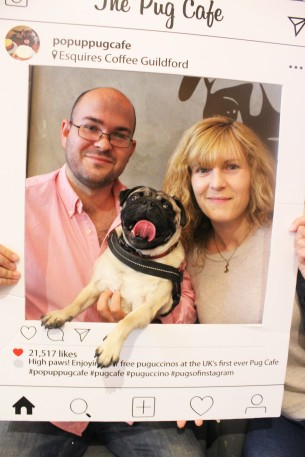 happy pug with his owners at pop up pug cafe