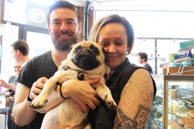 lady looks at pug lovingly at pop up pug cafe