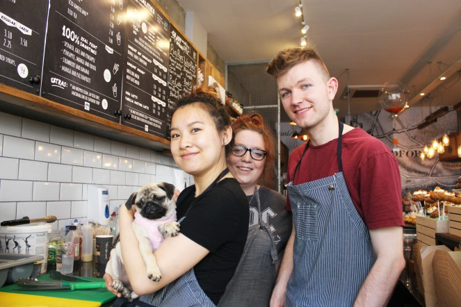 girl holds pug puppy at pop up pug cafe