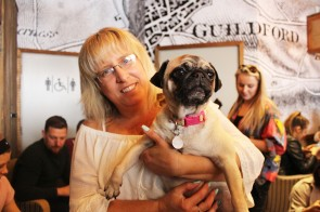 owner holds her pug baby at pop up pug cafe