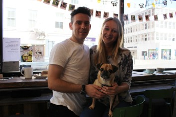 a couple with their pug cross at pop up pug cafe