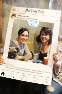 ladies look through a frame at pop up pug cafe