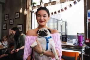girl holds pug at pop up pug cafe